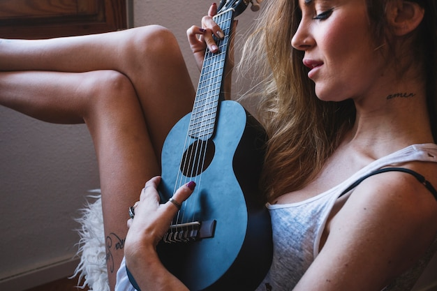 Schöne frau mit ukulele