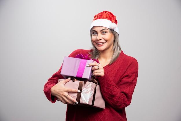Schöne frau mit weihnachtsgeschenken, die auf grauem hintergrund aufwerfen.
