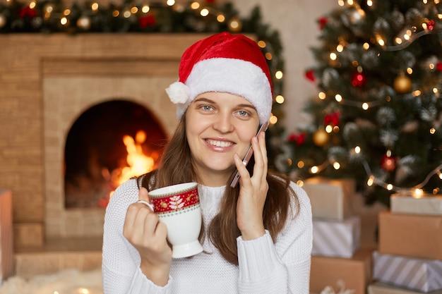 Schöne frau mit weihnachtsmütze, die heißes getränk trinkt, während sie mit jemandem telefoniert, grüßt mit neujahr, drückt glück aus, trägt weißen pullover, posiert innen nahe kamin und weihnachtsbaum