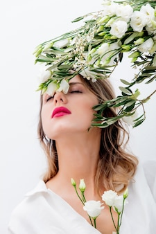 Schöne frau mit weißen rosen im ärmel, dressing in einem weißen kleid. frühlingskonzept oder valentinstag