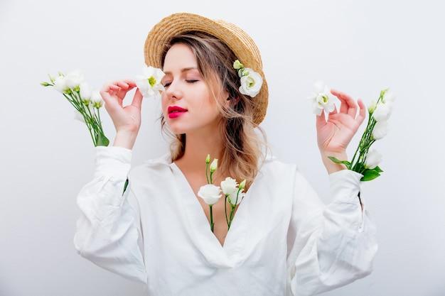 Schöne frau mit weißen rosen in den ärmeln im hut auf weißem hintergrund. frühlingskonzept oder valentinstag