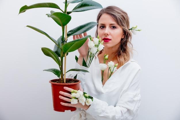 Schöne frau mit weißen rosen in den ärmeln mit pflanze. frühlingskonzept oder valentinstag