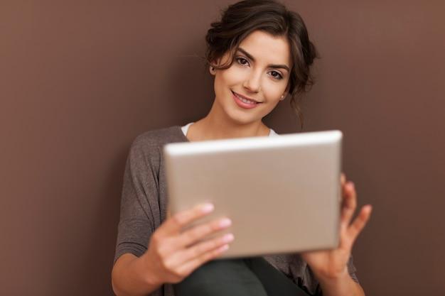 Schöne frau mit zeitgenössischem digitalem tablett