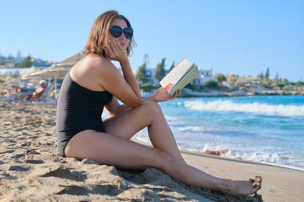 Schöne frau mittleren alters, die auf meer ruht, sommerfrau, die auf sandigem uferlesebuch sitzt, sonnenbäder in untergehender sonne, goldene stunde am strand, kopienraum