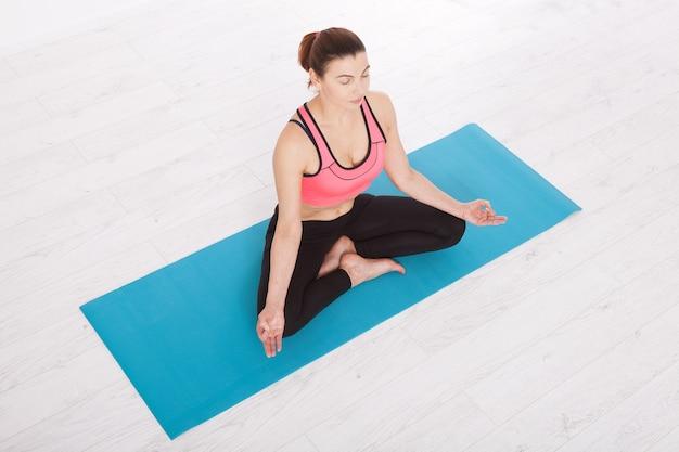 Schöne frau mittleren alters, die yoga drinnen tut. horizontale draufsicht.