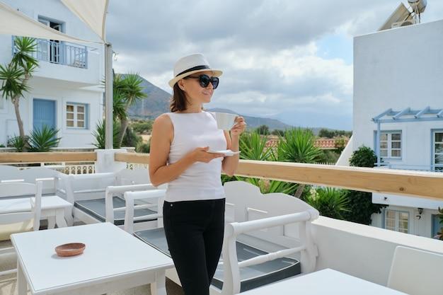 Schöne frau mittleren alters im urlaub im resort-spa-hotel, frau, die mit tasse kaffee ruht