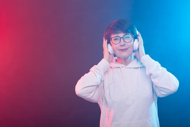 Schöne frau mittleren alters in einem weißen pullover und einer brille hört musik, während sie auf einem posiert