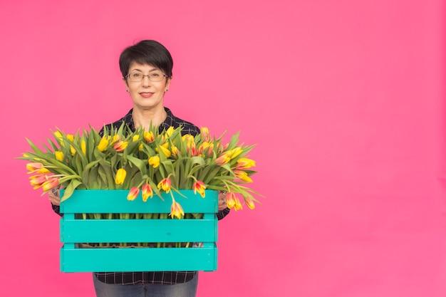 Schöne frau mittleren alters mit gelben tulpen auf rosa hintergrund mit kopienraum