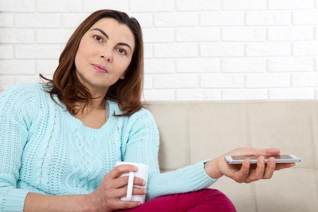Schöne frau mittleren alters mit tasse kaffee und smartphone entspannen zu hause.