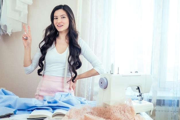 Schöne frau näherin mit langen haaren hält schere in ihren händen. schneider kreiert eine kleiderkollektion auf dem hintergrund einer nähmaschine. konzept der muse, idee und inspiration