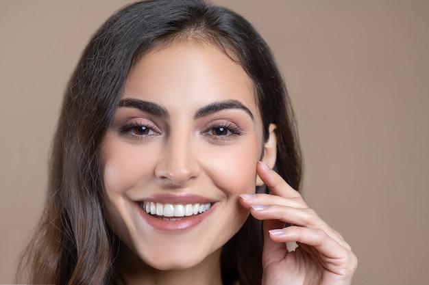 Schöne frau. nahaufnahmegesicht der jungen erwachsenen lächelnden schönen frau mit langen haaren, die finger zur wange berühren