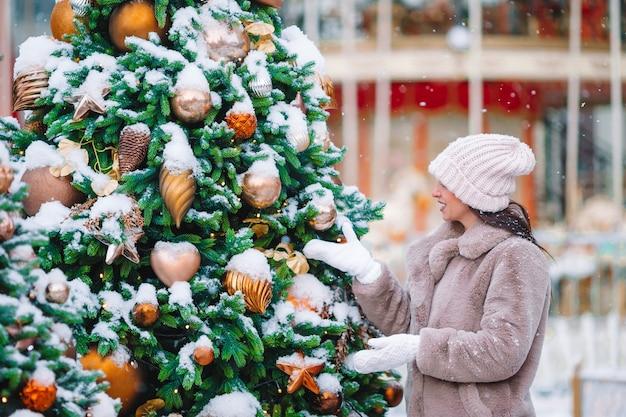 Schöne frau nahe weihnachtsbaum im schnee draußen