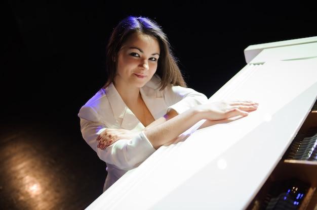Schöne frau nahe weißem klavier om die szene