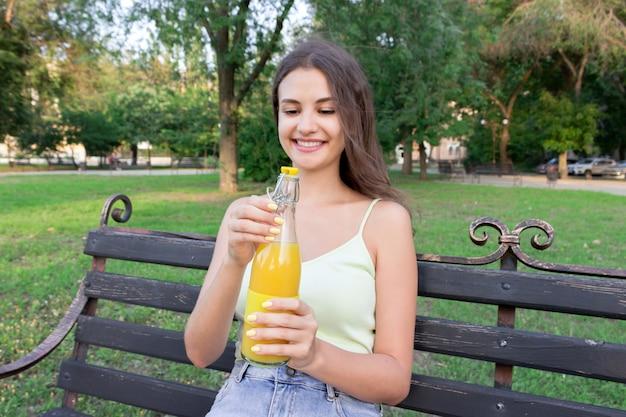 Schöne frau öffnet am heißen sommertag eine flasche frischen kalten saftes auf der bank im park.