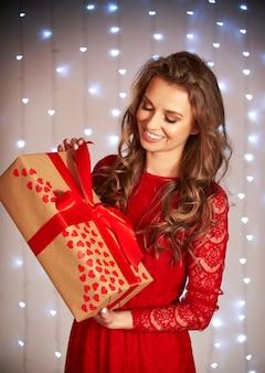 Schöne frau öffnet ein geschenk