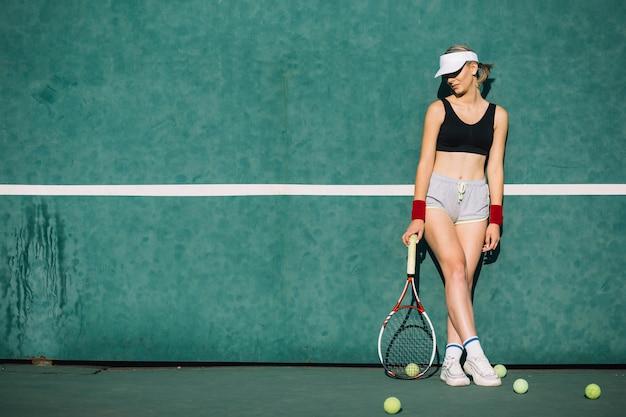 Schöne frau posiert auf einem tennisplatz