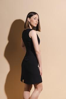 Schöne frau posiert im schwarzen kleid