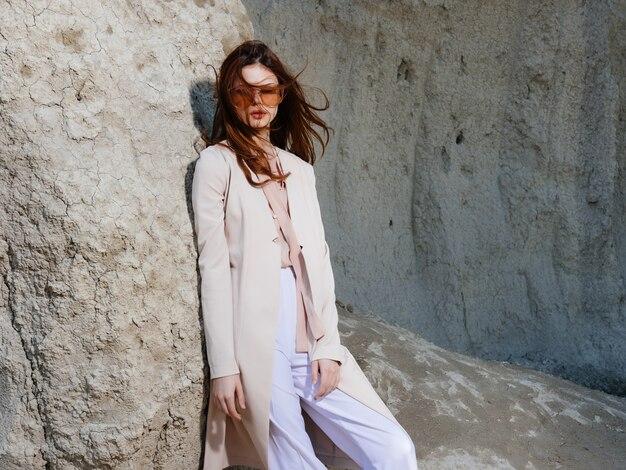 Schöne frau posiert in der nähe von felsen in der sand-lifestyle-mode