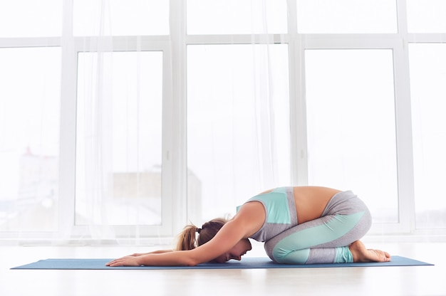 Schöne frau praktiziert yoga asana balasana - kinderpose im yoga-studio
