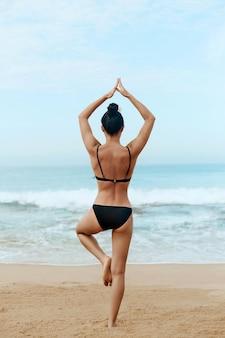 Schöne frau praktiziert yoga und meditiert am strand. mädchen, das yoga tut. aktiver lebensstil. gesundes und yoga-konzept.