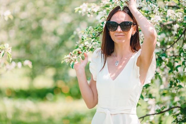Schöne frau riechen blühenden baum der frühlingsstimmung, der naturblumengarten der natur genießt