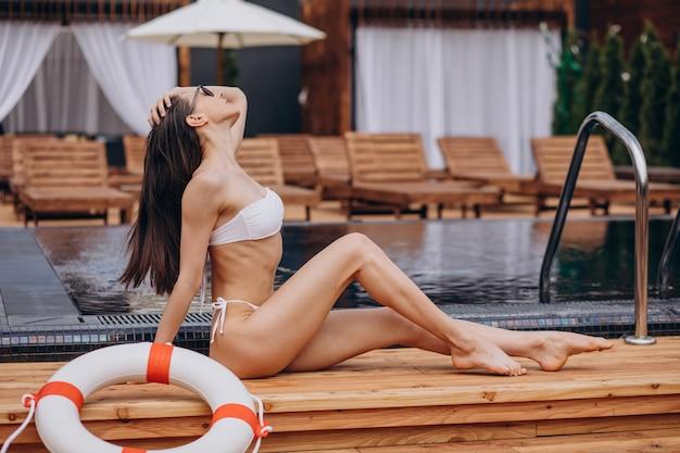 Schöne frau ruht am pool mit rettungsring