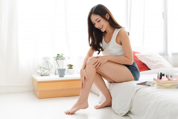 Schöne frau schönheit gesundheitspflege. schönheit und spa. perfekte frische haut. frau, die feuchtigkeitscreme auf lange beine zu hause aufträgt