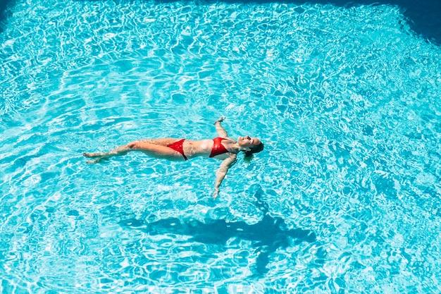 Schöne frau schwimmt am blauen pool und genießt sommerferien und gesunden lebensstil