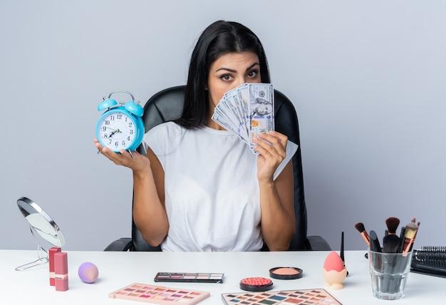 Schöne frau sitzt am tisch mit make-up-tools und hält wecker bedecktes gesicht mit bargeld