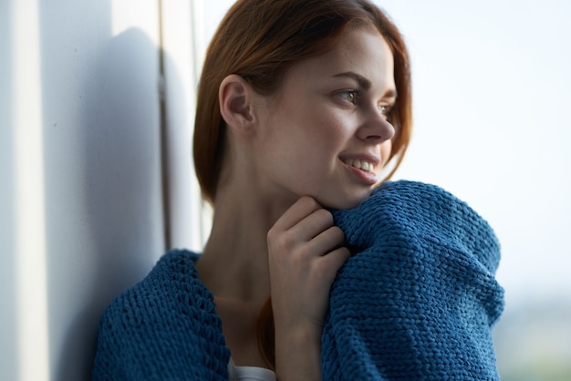 Schöne frau sitzt auf der fensterbank mit einem blauen plaid