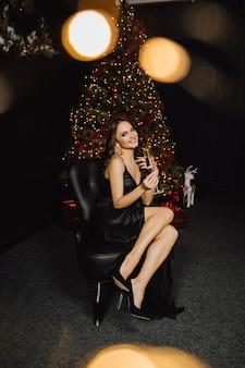 Schöne frau sitzt auf einem stuhl auf einem weihnachtsbaumhintergrund, lächelt und hält ein glas mit champagner