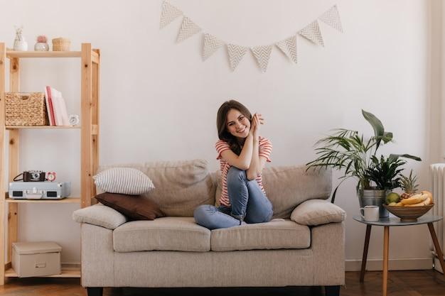 Schöne frau sitzt bequem auf der couch und mit lächeln posiert in der hellen wohnung