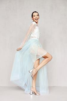 Schöne frau spielt mit saum von transparenten blassen kleidern mit spitze