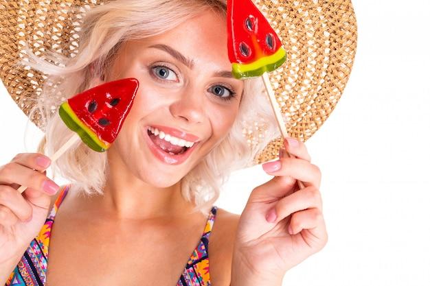 Schöne frau steht im badeanzug mit wassermelonenlolipops und lächelt isoliert auf weiß