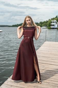 Schöne frau steht mit langem dunkelrotem kleid in der natur. reisekonzept.
