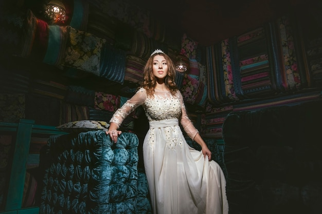 Schöne frau sultana kleid schmuck tiara im orientalischen stil und im interieur