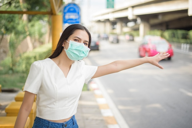 Schöne frau trägt gesichtsmaske in bushaltestelle