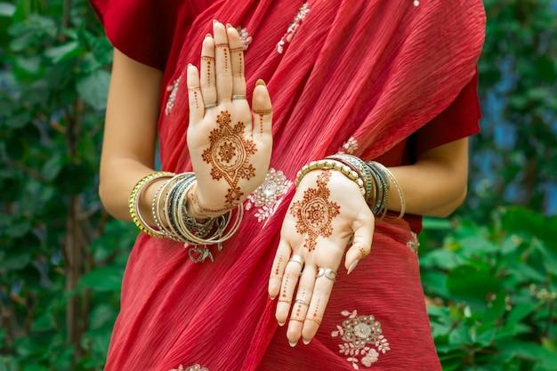 Schöne frau tragen traditionelle muslimische arabische indische hochzeit rot rosa sari kleid hände mit henna tattoo mehndi muster schmuck armbänder tun hände tanz bewegung. fest des feiertagskulturfestivals