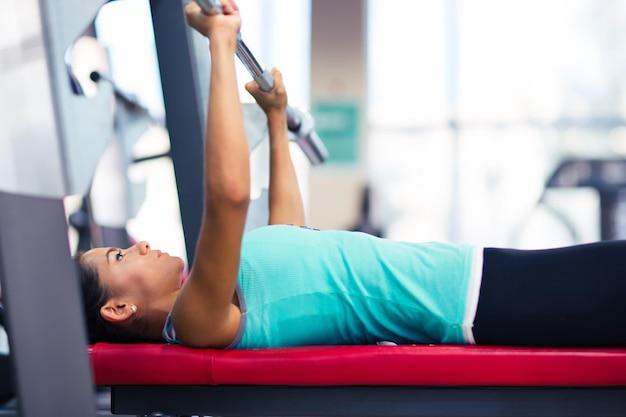 Schöne frau trainieren mit langhantel auf der bank im fitnessstudio