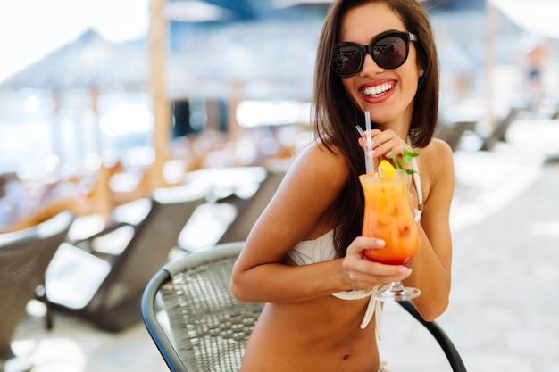 Schöne frau trinkt cocktail im sommer und lächelt
