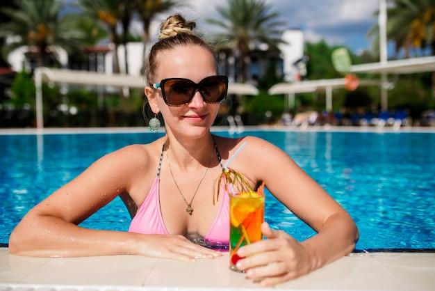 Schöne frau trinkt einen cocktail im pool