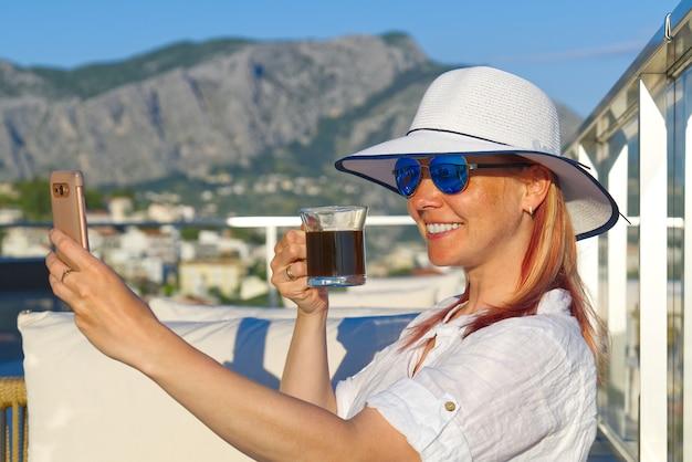 Schöne frau trinkt frischen kaffee mit strohhut in der lounge-zone im freien hotel spa resort