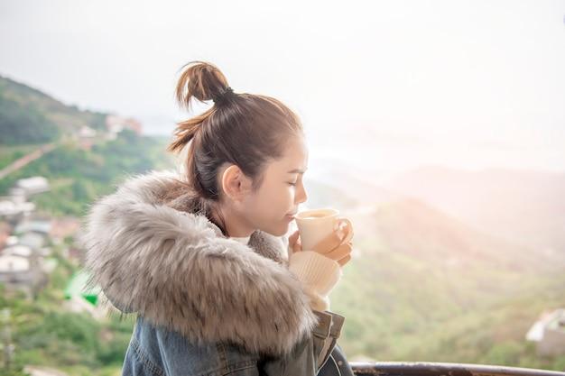 Schöne frau trinkt kaffee morgens mit naturhintergrund