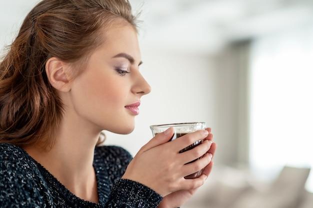 Schöne frau trinkt kaffee und genießt den geschmack. hübsches junges erwachsenes mädchen, das mit tasse tee entspannt.