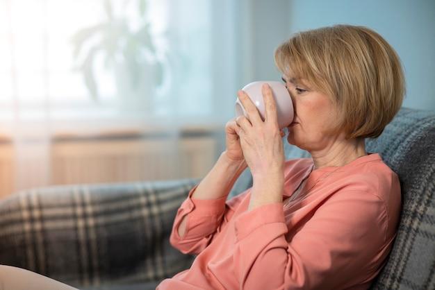 Schöne frau trinkt tee oder kaffee von einer tasse, die an der couch zu hause im wohnzimmer sitzt
