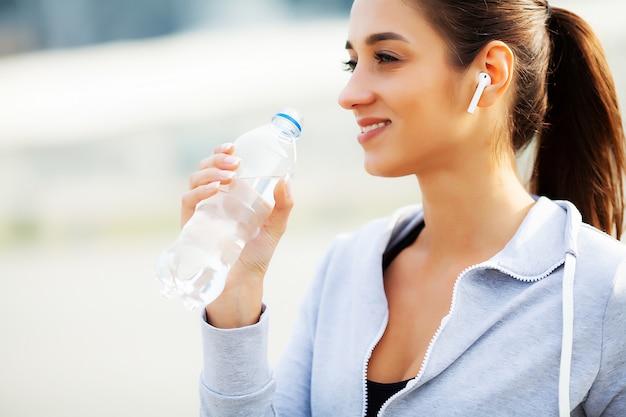Schöne frau trinkt wasser und hört musik nach dem laufen