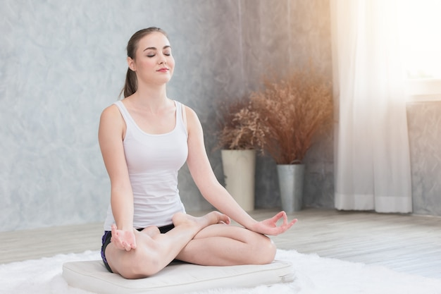 Schöne frau tut yoga sitzendes lotoskonzentrationsauge geschlossene haltung zu hause