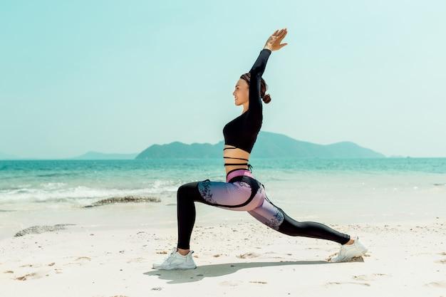 Schöne frau übt yoga am meer an einem sonnigen tag. die frau macht dehnübungen. hanteln liegend sand.