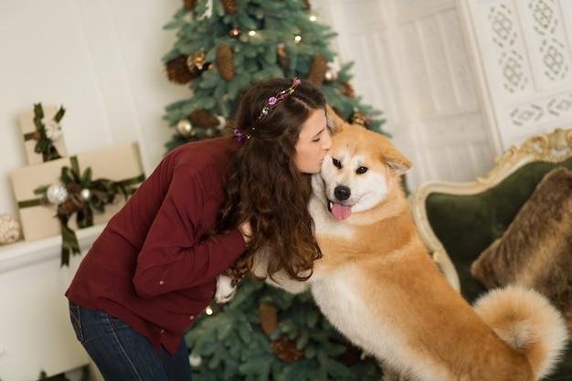 Schöne frau umarmt, kuschelt mit ihrem akita inu hund. auf dem hintergrund eines weihnachtsbaum kommode