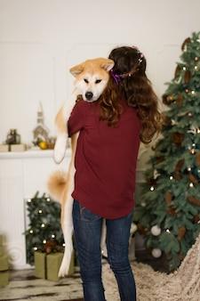 Schöne frau umarmt, kuschelt mit ihrem akita inu hund. vor dem hintergrund eines weihnachtsbaum kommode mit kerzen in einem dekorierten raum. frohes neues jahr und frohe weihnachten